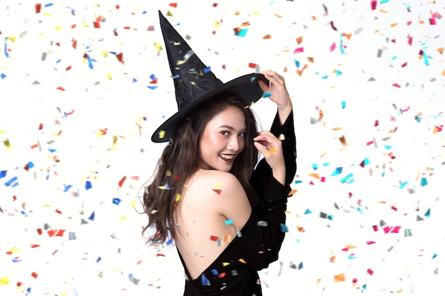 Beautiful young women in black witch halloween costumes on party over white background