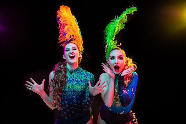 Beautiful young women in carnival and masquerade costume in colorful neon lights on black wall