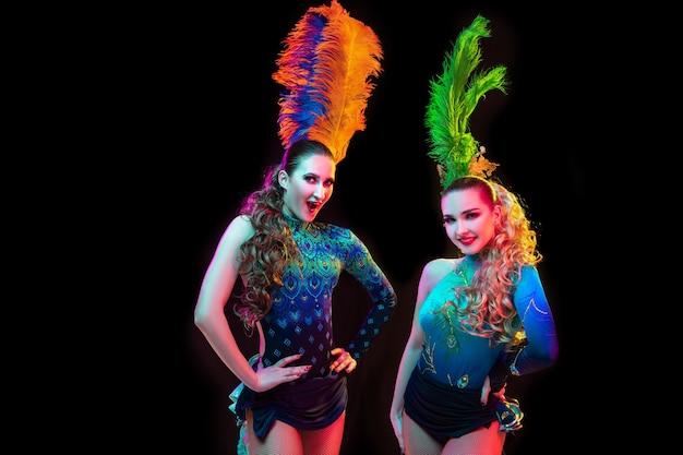 Belle giovani donne in carnevale, elegante costume in maschera con piume su sfondo nero in luce al neon.