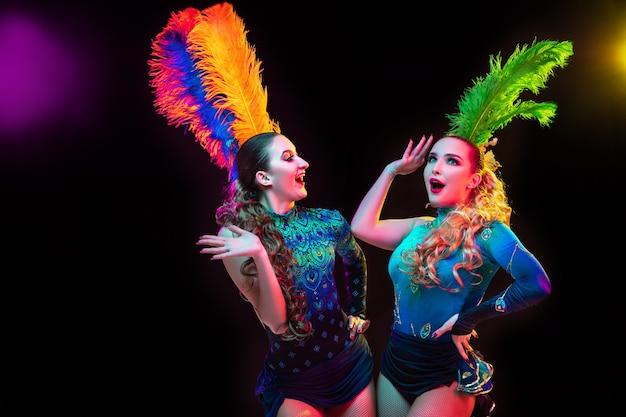 Belle giovani donne in carnevale, elegante costume in maschera con piume sul muro nero in luce al neon