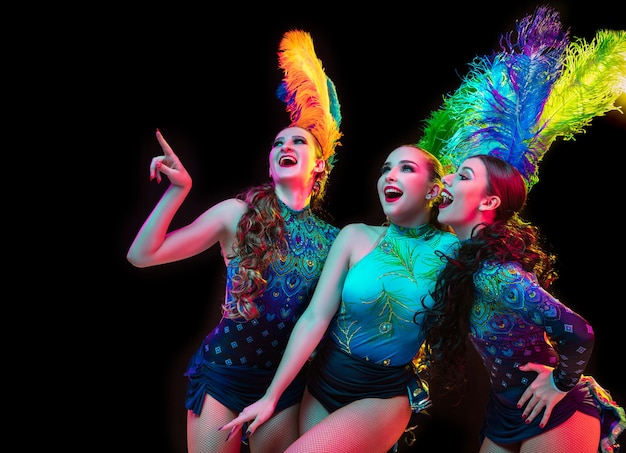 Beautiful young women in carnival, stylish masquerade costume with feathers on black wall in neon light