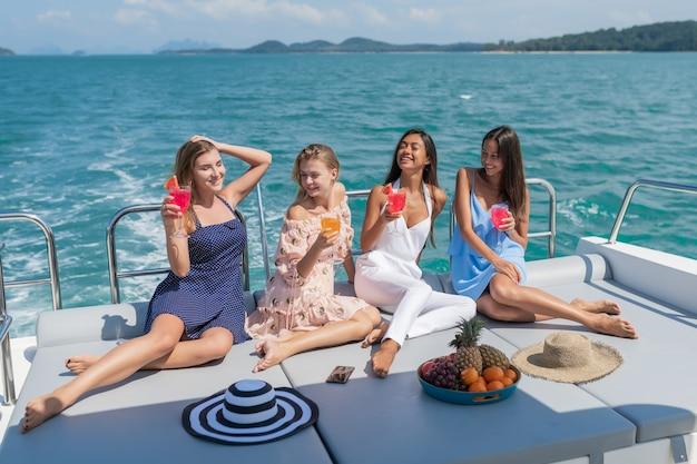 Красивые молодые женщины празднуют с напитками и фруктами на яхте