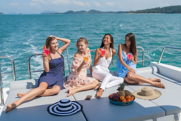 Beautiful young women celebrating with drinks and fruits on yacht