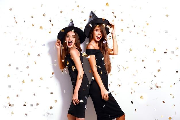 Красивые молодые женщины, одетые как ведьма для вечеринки на хэллоуин