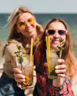 Красивые молодые женщины, наслаждаясь летними коктейлями