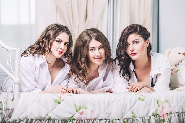 Красивые молодые женщины друзья болтают в спальне в белых рубашках