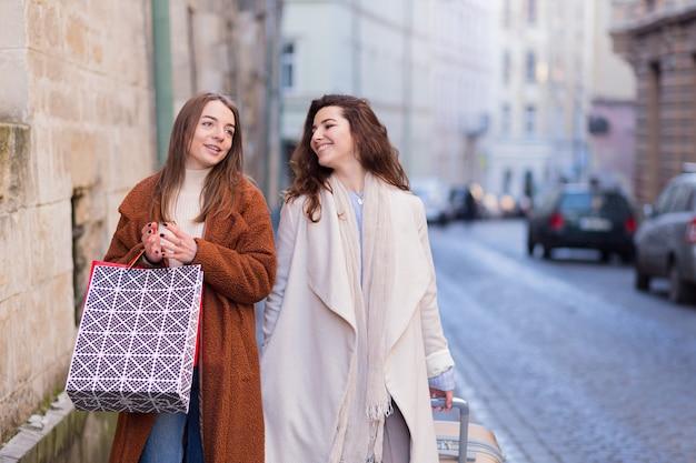 Красивые молодые девушки подруги с чемоданом и шоппингом ходят по городу в поисках отеля