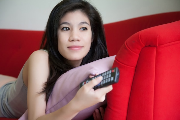 Beautiful young women holding remote tv on red sofa