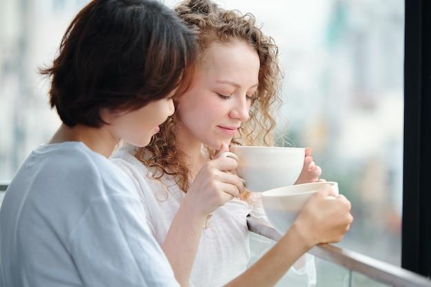 バルコニーで朝のコーヒーを飲むのが大好きな美しい若い女性