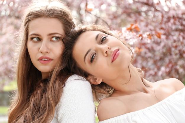 Красивые молодые женщины в парке с цветущими деревьями в весенний день