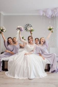 Красивые молодые женщины в шелковых рубашках веселятся накануне свадьбы подруги. поздравить невесту, дружба