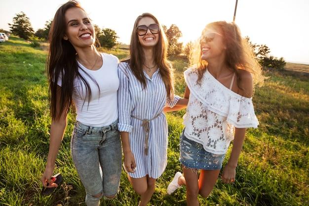 Красивые молодые женщины в солнечных очках, одетые в красивую одежду, стоят в поле и улыбаются в солнечный день. .