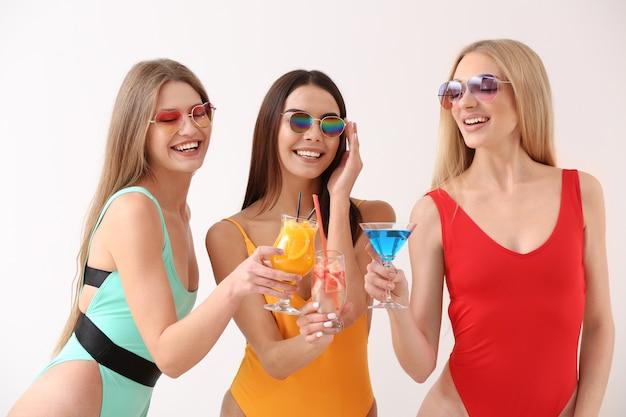 Красивые молодые женщины в купальных костюмах и с коктейлями на белом фоне