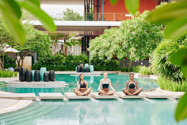 Beautiful young women meditating with eyes closed on stones in swimming pool of spa hotel
