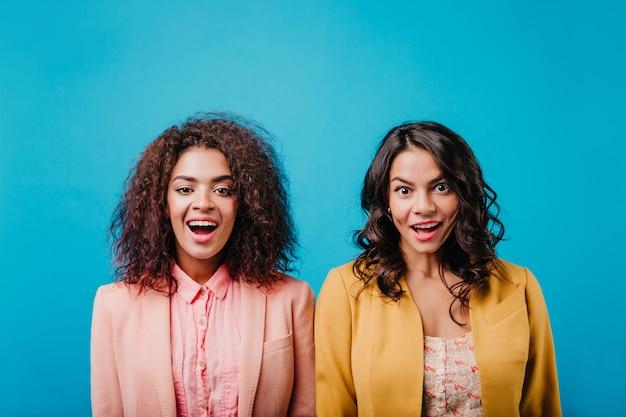 Красивые молодые женщины позируют на синей стене