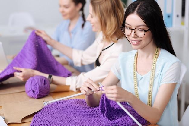 아틀리에의 테이블에 앉아 큰 뜨개질 바늘을 사용하여 보라색 실로 스카프를 뜨개질 아름다운 젊은 여성.