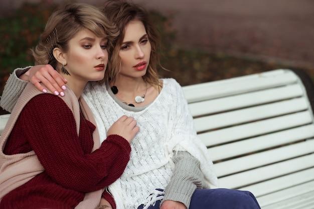 秋の公園のベンチに座っている美しい若い女性