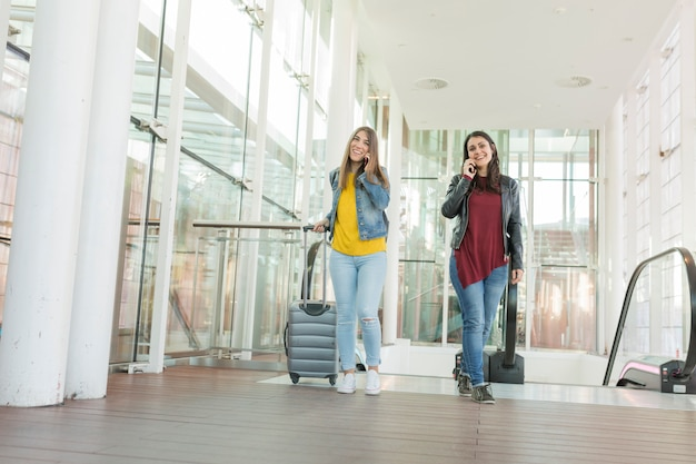 Beautiful young women talking on her mobile phone and smiling. travel concept at the airport, she is going up stairs with a trolley. friends and lifestyle