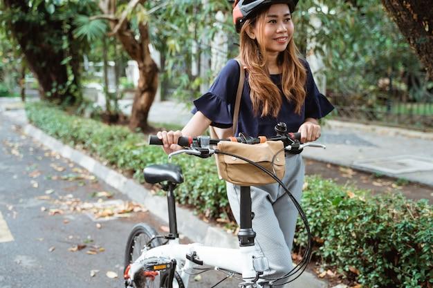 美しい若い女性は折りたたみ自転車の上を歩く