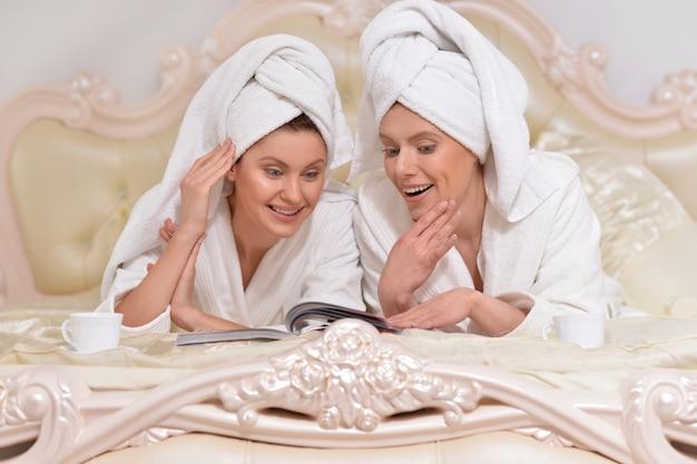 침대에서 잡지를 읽는 흰색 목욕 가운을 입은 아름다운 젊은 여성