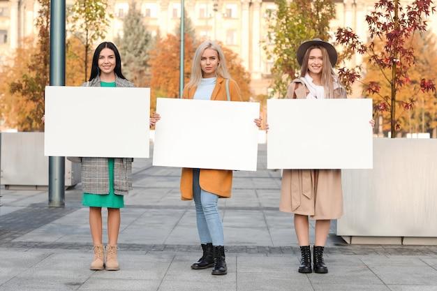 야외에서 빈 포스터와 아름 다운 젊은 여성