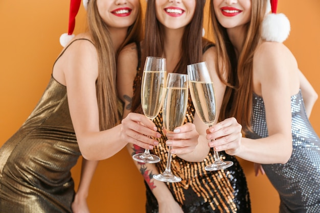 Beautiful young women with champagne celebrating christmas on color