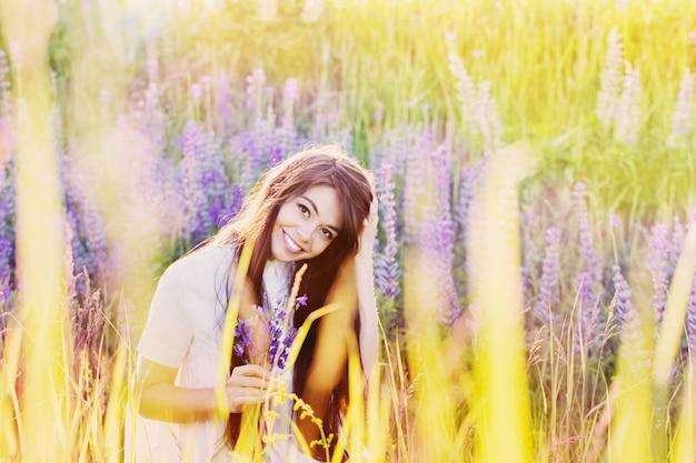 屋外の花を持つ美しい若い女性