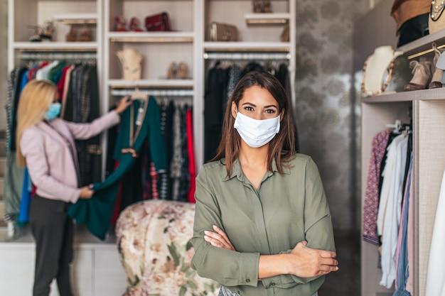 高価なブティックや店でエレガントな服を試着する保護フェイスマスクを持つ美しい若い女性。