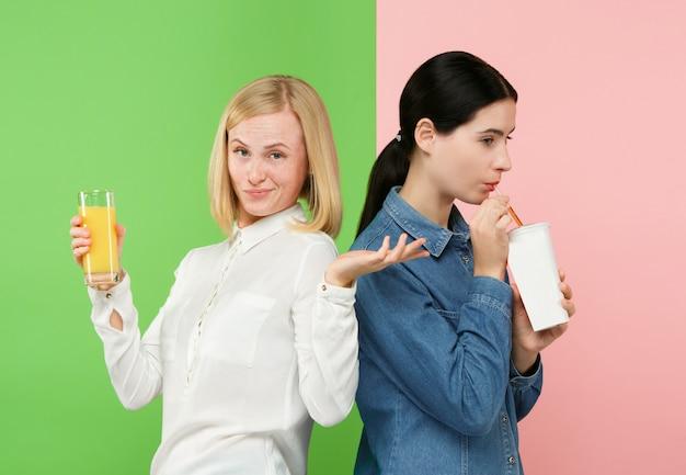 Рацион питания. концепция диеты. здоровая пища. beautiful young women выбирают между фруктовым апельсиновым соком и газированным сладким напитком