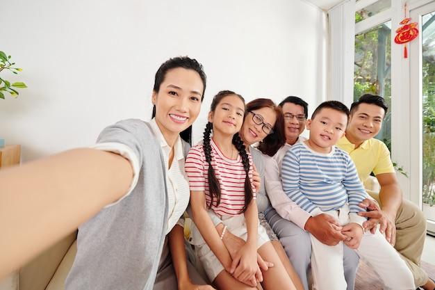 Красивая юонг азиатская женщина, делающая селфи со своими родителями, мужем и детьми, когда они собрались дома