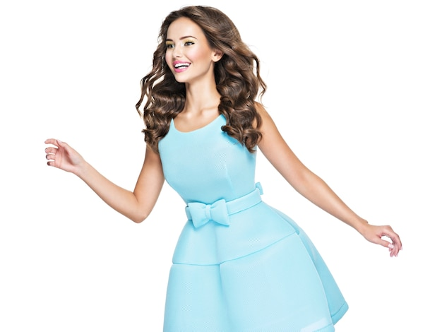 Bella donna felice in abito blu lunghi capelli castani. felice donna alla moda con emozioni espressive.