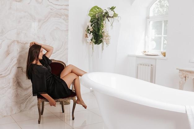 화장실 근처 바닥에 앉아 실크 잠옷에 긴 머리를 가진 beautifull 갈색 머리 여자