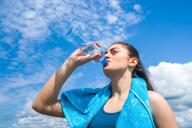 Beautifull girl runner is having break, drinking water against clear blue sky.