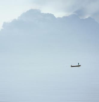 Красивая природа с большим расстоянием рыбака на лодке в гладком море и чистом небе, эффект размытия движения и минимализм.