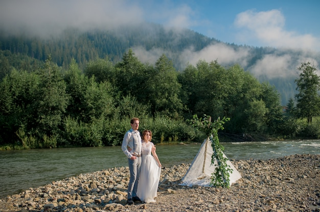 完璧な景色と山の近くに立っている美しい結婚式のカップル
