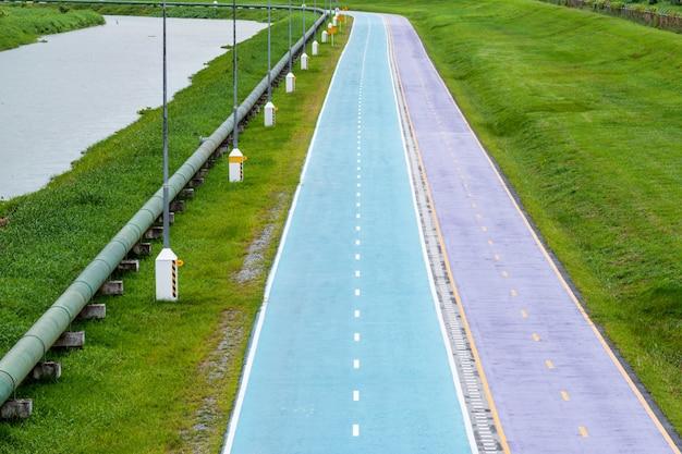 運河と緑の芝生に沿った公園の美しい色のサイクリングレーン。