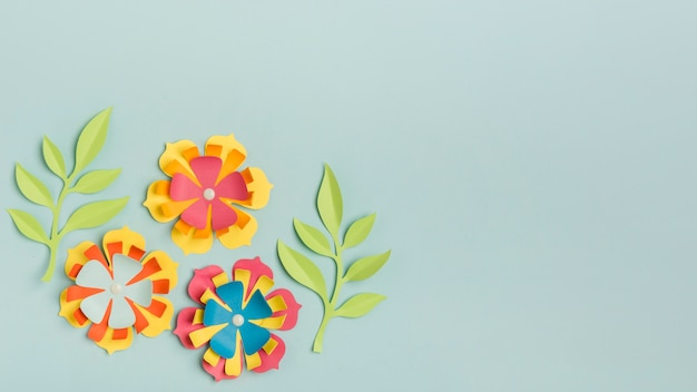 Beautifully colored paper spring flowers with copy space and leaves