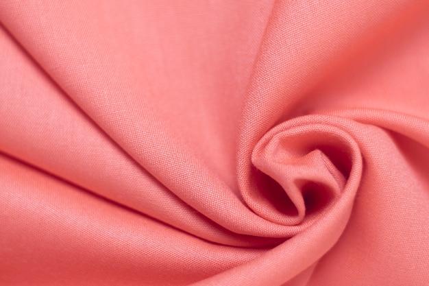 Красиво скомканная текстура розовой ткани.