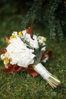 Beautifully decorated bride's bouquet lies on the green grass.