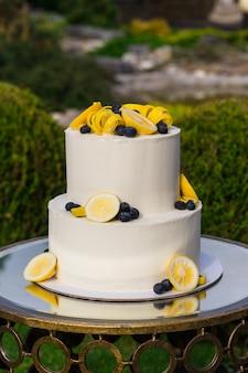 Красиво оформленный торт на подставке на свадебной церемонии на природе