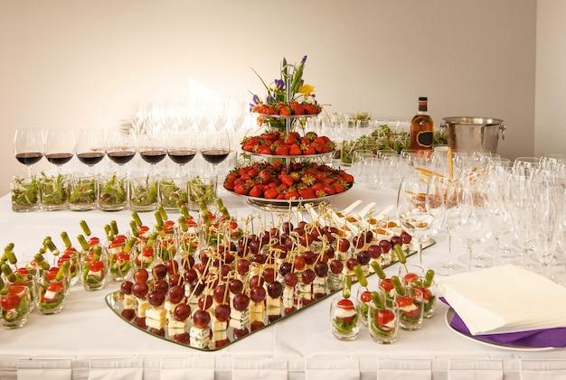 버거, 프로피테롤, 샐러드, 차가운 스낵으로 아름답게 장식된 케이터링 연회 테이블. 테이블에 다양하고 맛있는 맛있는 간식