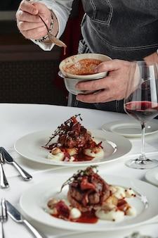다양한 음식 스낵과 애피타이저로 아름답게 장식 된 케이터링 연회 테이블. 요리사는 테이블에 접시를 넣습니다.