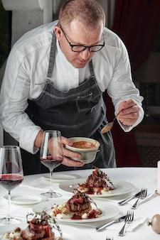 다양한 음식 스낵과 에피타이저로 아름답게 장식된 케이터링 연회 테이블. 요리사는 테이블에 접시를 넣습니다.