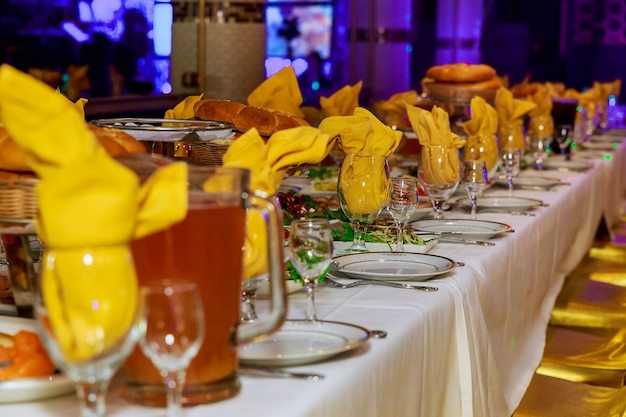 Красиво оформленный кейтеринг банкетный стол с различными закусками и закусками с бутербродом, икрой, свежими фруктами на корпоративе или свадебном торжестве.