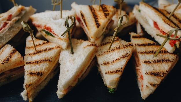 美しく装飾されたケータリングバンケットテーブル、さまざまなスナックと前菜とサンドイッチ