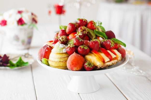 Beautifully decorated catering serving of fresh fruits on white wooden table