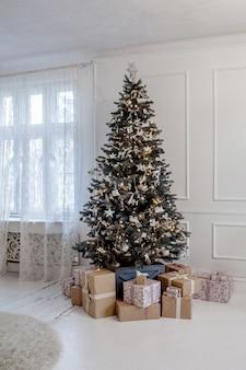 その下にたくさんのプレゼントがある美しく装飾されたクリスマスツリー。