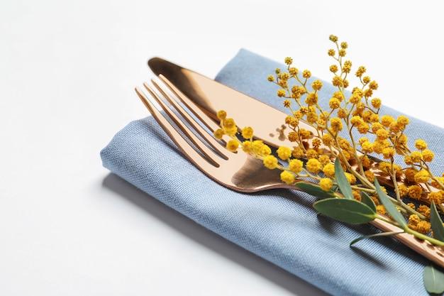 白のミモザとイースターテーブルセッティングのための美しく装飾されたカトラリー