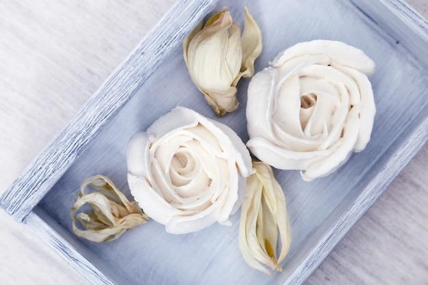 美しく装飾されたデザート。テーブルの上の木製の青い箱に花の形をした白いメレンゲ。低カロリーの甘さ。アップルゼファー。上面図。