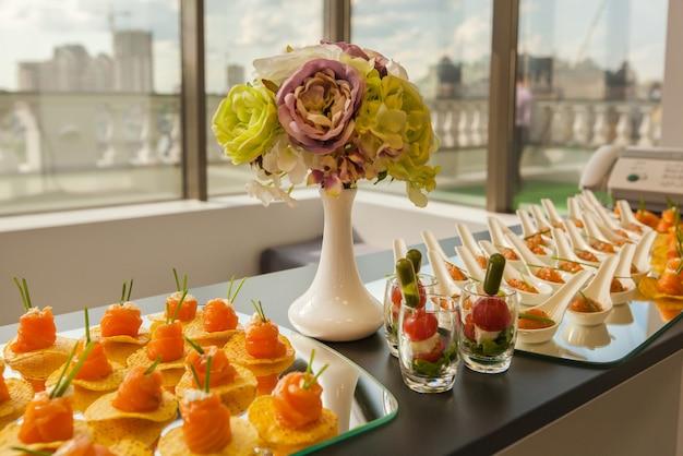 햄버거 프로페테롤 샐러드와 감기가 있는 미식을 위해 아름답게 장식된 축제 테이블